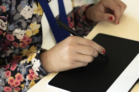 Closeup view of little girls right hand holding a plastic pen to draw a picture on white electronic pad Reklamní fotografie