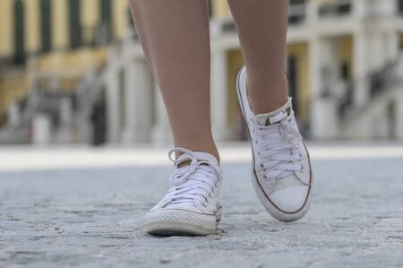legs of a girl walking on the asphalt in white sneakers. modern young woman with slender beautiful legs in fashionable white sneakers walks down the street. stylish sporty women's shoes. summer style. closeup of female legs with shoes