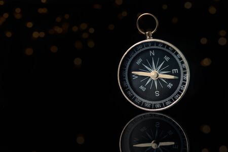 Compass on dark black background with copy space using as direction
