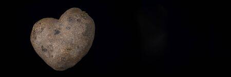 heart shaped potato on black background