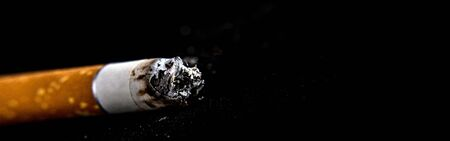Cigarette butt on a black background. Panoramic image