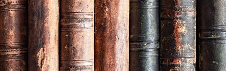 stack of old books on a library shelf. Panoramic image