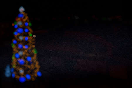 Bokeh christmas tree on dark background. Abstract christmas background with defocused lights. 免版税图像