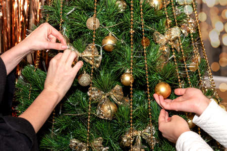 Mom and daughter decorate the Christmas tree. Close-up. Hands only