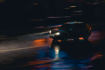 The car drives in the night city in the rain. Motion blur image