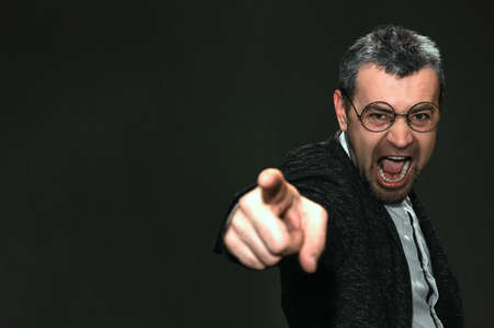 Portrait of an angry man with glasses on a dark background. Male screams angrily at someone, being irritated