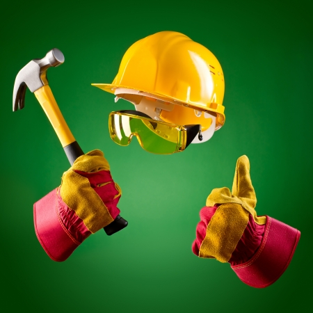 invisible builder in a helmet and with a hammer on a green background Stock Photo