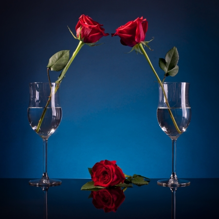 three roses in glasses on a blue background photo