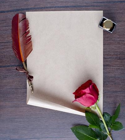pluma de escribir antigua: l�piz y papel viejo con una rosa sobre una mesa de madera Foto de archivo