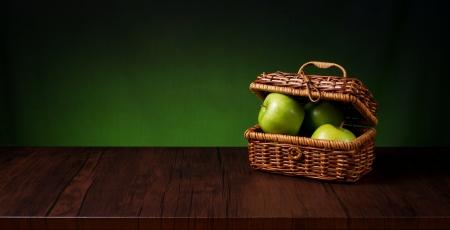 木製のテーブルのりんごのバスケット 写真素材