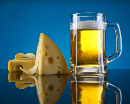 beer, cheese and chips on a blue background with a mirror photo