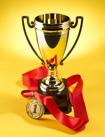 golden cup and medal for the first place on a yellow background