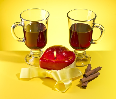 beguin: candle in the form of hearts, glasses of mulled wine and cinnamon on a yellow background