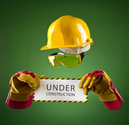 invisible builder in a yellow helmet with an information banner on a green background photo