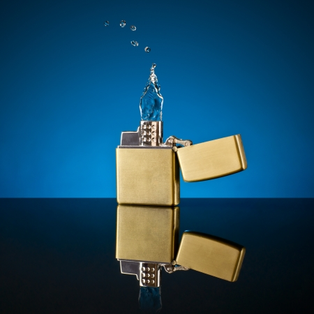 lighter and the flame out of the water on a blue glass background
