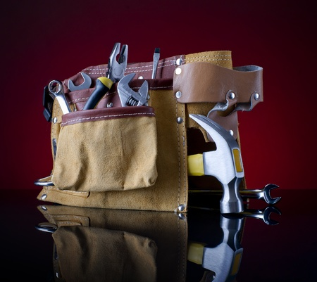 handtool: tool belt and hammer on red glass background