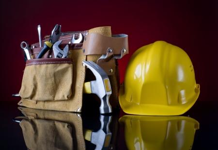 ツール ベルトと赤いガラスの背景に黄色いヘルメット 写真素材