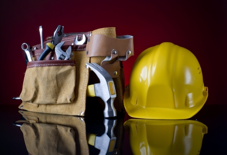tool belt and a yellow helmet on a red glass background Standard-Bild