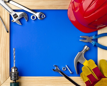 home improvements: tools and helmet on a blue background in a wooden frame