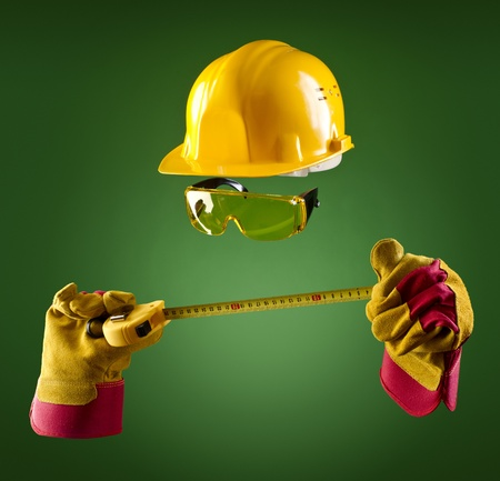 invisible builder in a helmet and with a tape measure on a green background