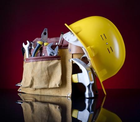 ツールベルト、ハンマー、赤いガラスの背景に黄色いヘルメット