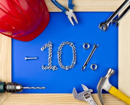casco rojo: herramientas y casco sobre un fondo azul en un marco de madera - 10 por ciento de descuento