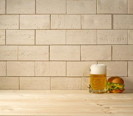 beige brick background, beer and burger on the wooden floor photo