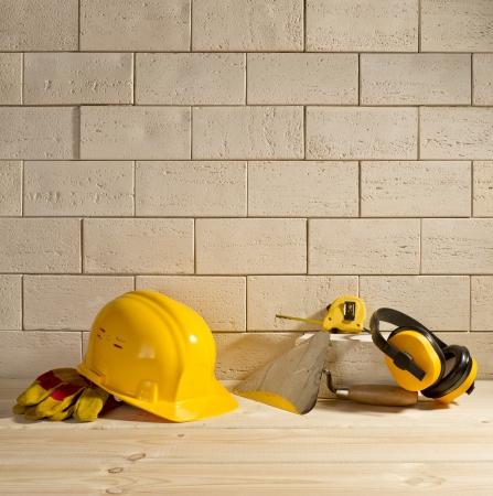 beige brick background, yellow helmet and trowel on a wooden floor Standard-Bild