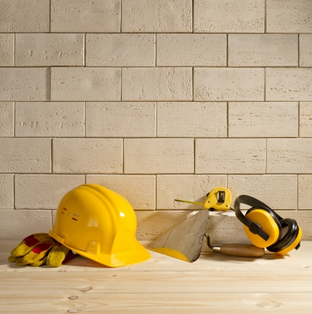 beige brick background, yellow helmet and trowel on a wooden floor photo