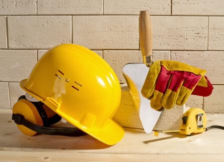 beige brick wall, yellow helmet and trowel on a wooden floor Standard-Bild