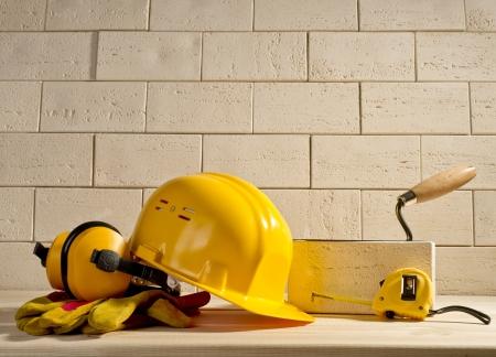 beige brick wall, yellow helmet and measuring tape on a wooden floor Standard-Bild