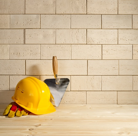 beige brick background, trowel and helmet on a wooden floor photo