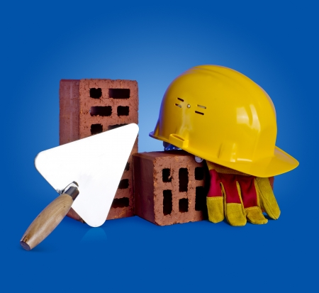 bricks, trowel and helmet on a blue background photo