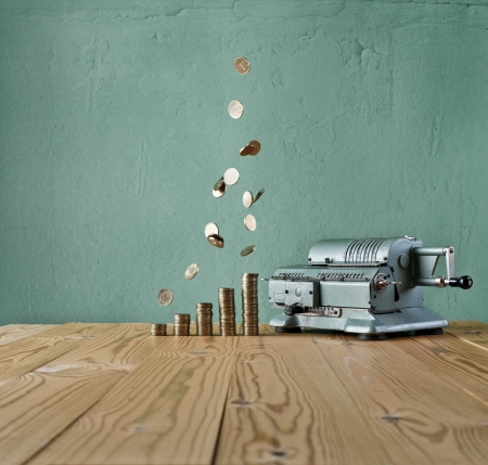 vintage calculator and money rain against the background of the old wall and wood table photo