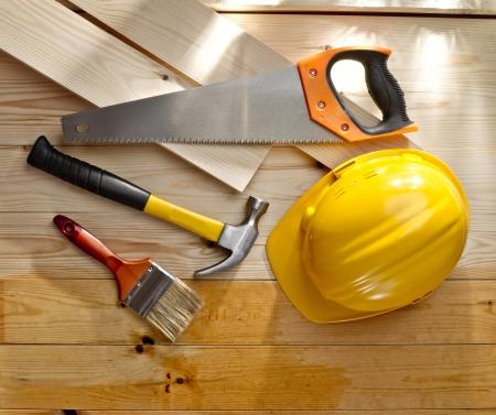 木製の床、ブラシ、のこぎり、ハンマーとヘルメット