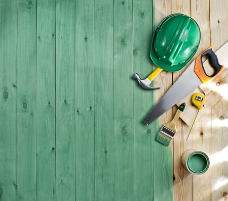 green wood floor with a brush, paint, tools and helmet