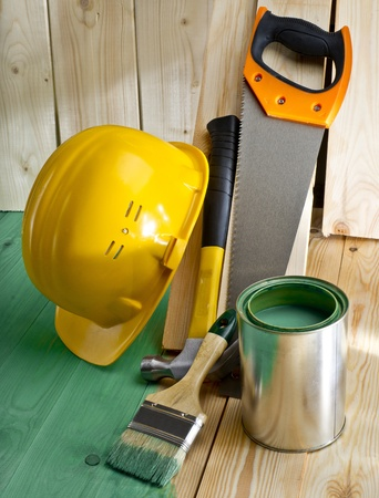 green wood floor with a brush, saw, hammer and helmet Stock Photo - 19666837