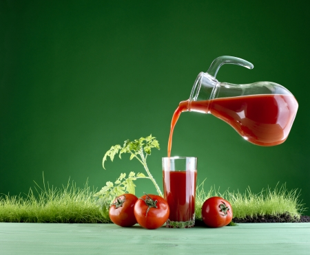 tomato juice and tomatoes on a background of green grass