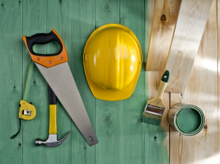 green wood floor with a brush, paint, saw, hammer and helmet Stock Photo - 19821731