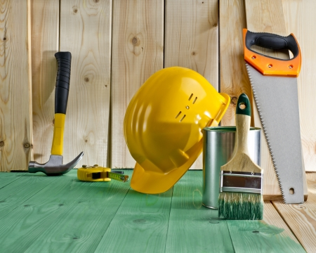 green wood floor with a brush, paint, saw and yellow helmet Stock Photo - 20294990