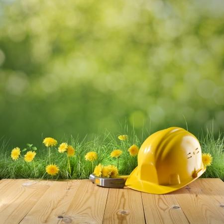 建設ヘルメットと緑の自然の背景にハンマー
