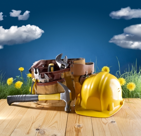 construction tool belt and helmet on blue nature background Stock Photo