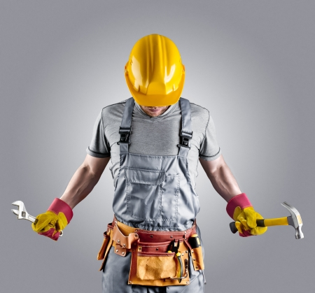 builder in a helmet with a hammer and a wrench photo