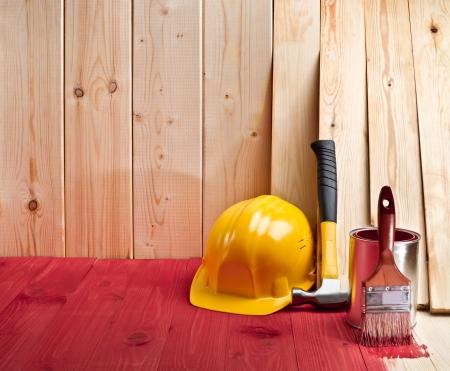 木製の床と壁のブラシ、塗料、ハンマー、黄色のヘルメットと