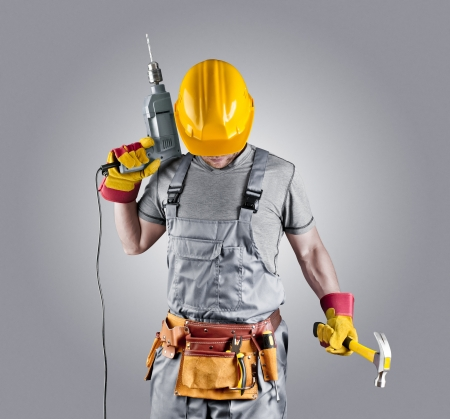 fitter: builder in a helmet with a hammer and a drill