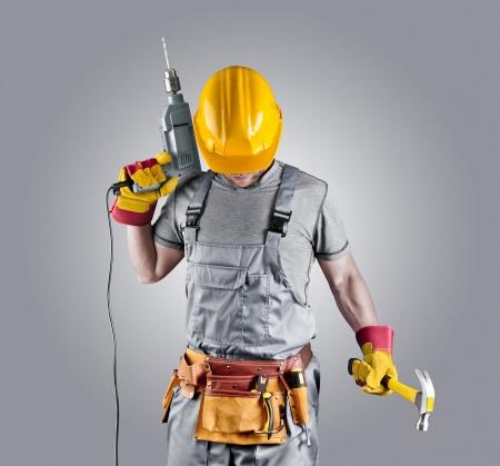 Costruttore in un casco con un martello e un trapano Archivio Fotografico - 21859184