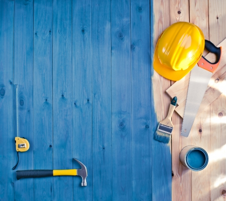 decoration work: blue wood floor with a brush, paint, tools and helmet Stock Photo