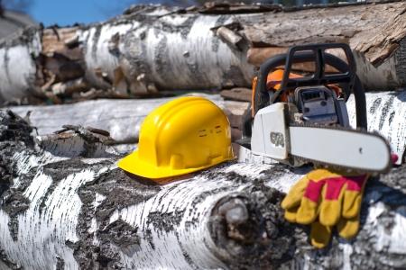 ヘルメットと木材のテクスチャの背景のチェーンソー