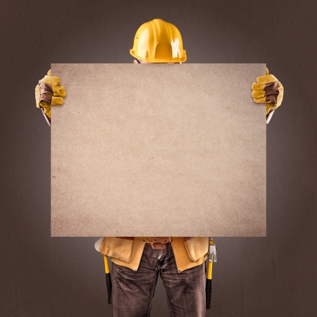 mounter: construction worker with information posters on a brown background Stock Photo