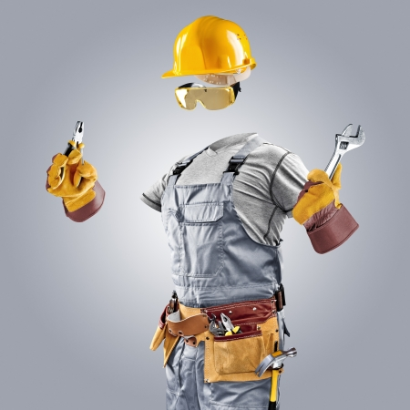 invisible builder with wrench and pliers on grey background